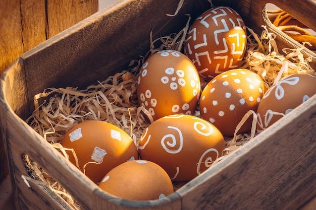 Semana santa en el campo. texturas naturales de granja con cálidos tonos de luz solar. huevos marrones con patrones blancos