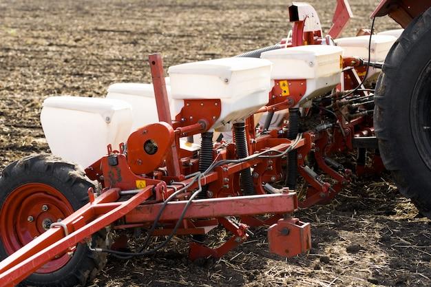 Sembradora tractor en un campo de tierra negra con una semilla arrastrada taladros agrícolas