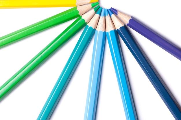 Un semicírculo de lápices afilados azules y verdes sobre un fondo blanco.
