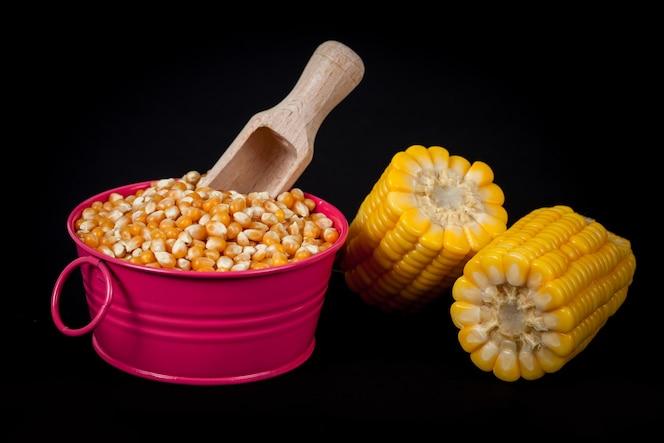 Semilla de maíz amarillo fresco en cubo en negro
