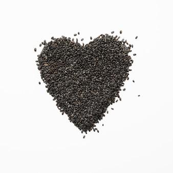 Semillas de albahaca en forma de corazón en blanco. imagen cuadrada.
