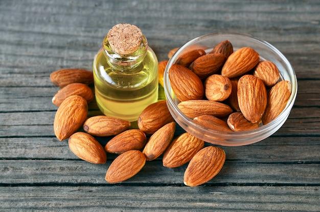 Semillas de almendras y aceite de almendras sobre fondo de madera vieja para una alimentación saludable, belleza y spa. enfoque selectivo.