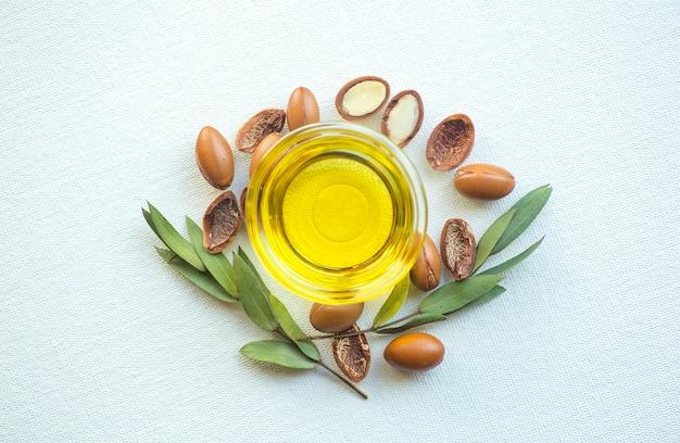 Semillas de argán y aceite aislado sobre un fondo blanco. nueces de aceite de argán con planta.