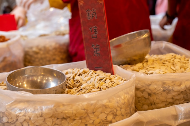 Semillas de calabaza chinas vendidas en la calle durante el festival de primavera el texto es: primero las ventas