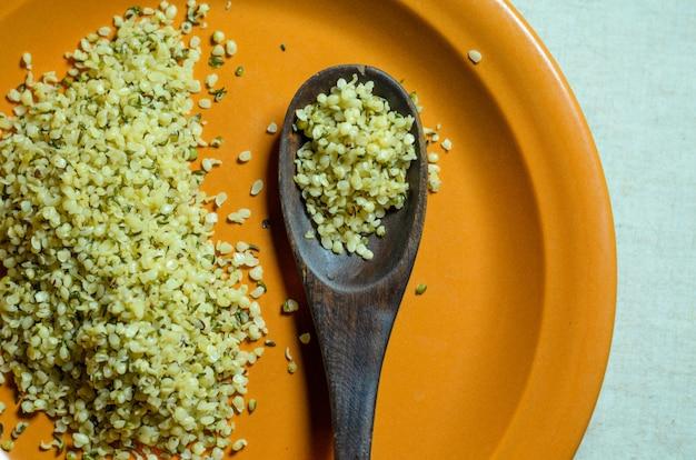 Semillas de cáñamo alimentos saludables en un plato de cerámica naranja con una cuchara de madera