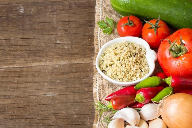 Semillas de cáñamo orgánico crudo en un tazón con verduras de cerca en una mesa de madera con espacio de copia