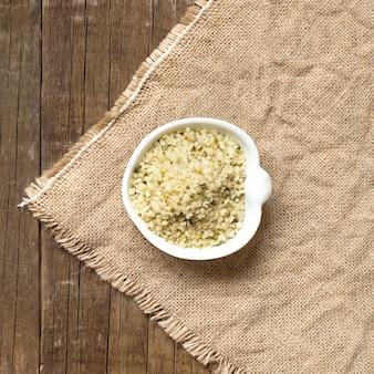 Semillas de cáñamo orgánico crudo en una vista superior del tazón sobre una mesa de madera sobre arpillera