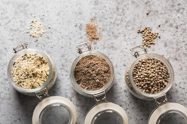 Semillas de cáñamo orgánico, harina, granos en frasco de vidrio sobre fondo gris. de cerca.