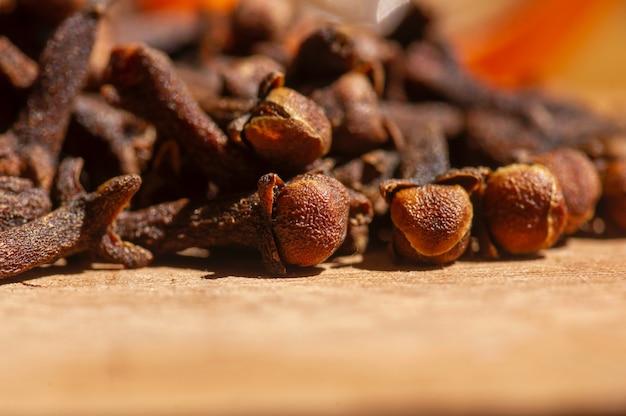 Semillas de clavo secas, en foco superficial, sobre la mesa de madera.