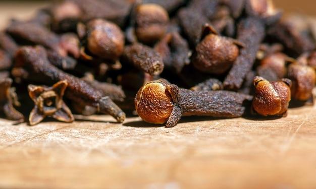 Semillas de clavo seco, en foco superficial, sobre la mesa de madera natural
