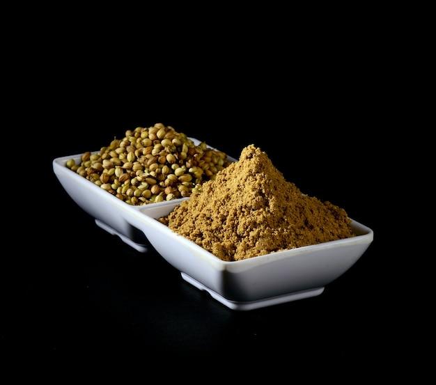 Semillas de coriandro y polvo de coriandro en plato blanco sobre fondo negro.