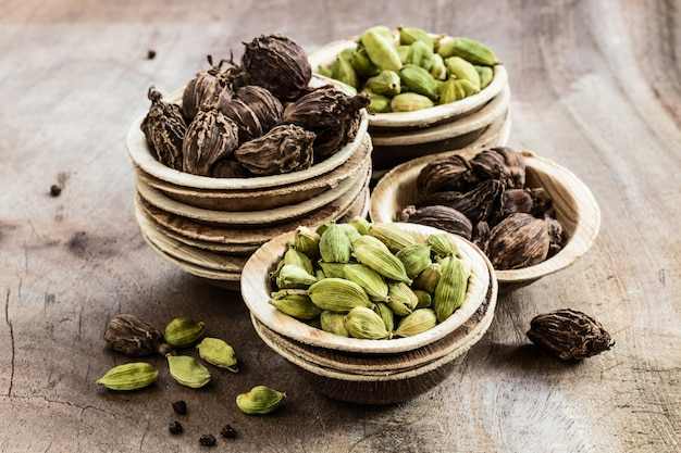Semillas enteras de cardamomo negro y verde en tazones de coco en madera