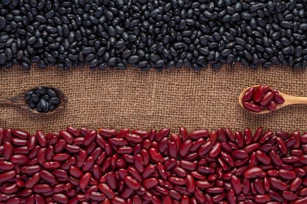 Semillas de frijol bicolores colocadas en un piso de madera marrón.