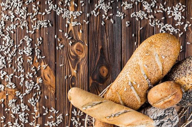 Semillas de girasol dispersas y cesta de pan sobre fondo de madera