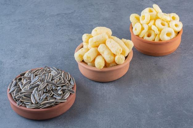 Semillas de girasol, palitos de maíz y anillo de maíz en tazones, sobre la superficie de mármol
