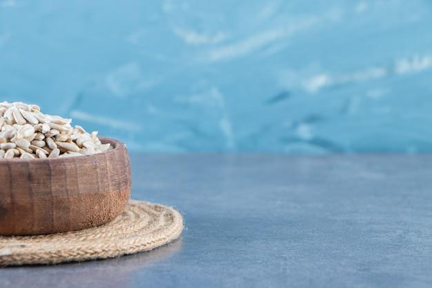 Semillas de girasol peladas en un recipiente sobre el salvamanteles, sobre el fondo de mármol.