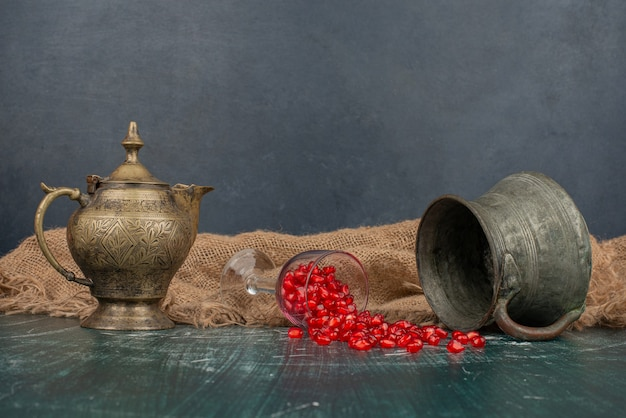 Semillas de granada esparcidas sobre una mesa de mármol con jarrón y tetera.