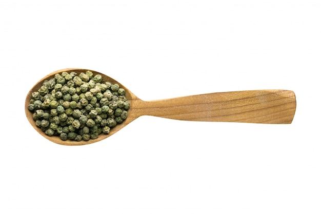 Semillas de grano de pimienta verde en la cuchara de madera aislada sobre fondo blanco. especias para cocinar alimentos, vista superior.
