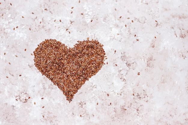 Semillas de lino en forma de corazón sobre fondo de hormigón con espacio para copia, vista superior
