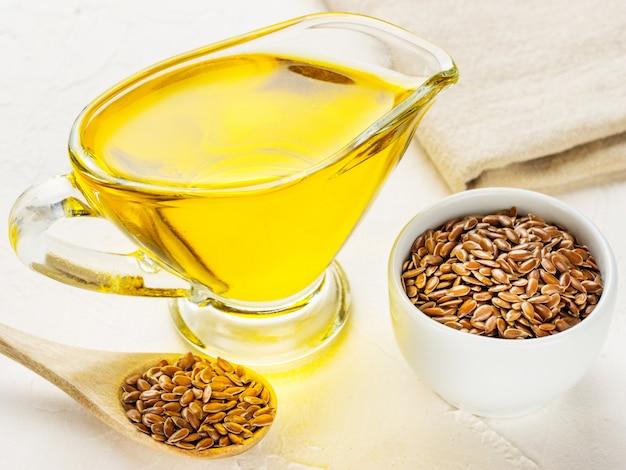 Semillas de lino marrón en una cuchara y aceite de linaza