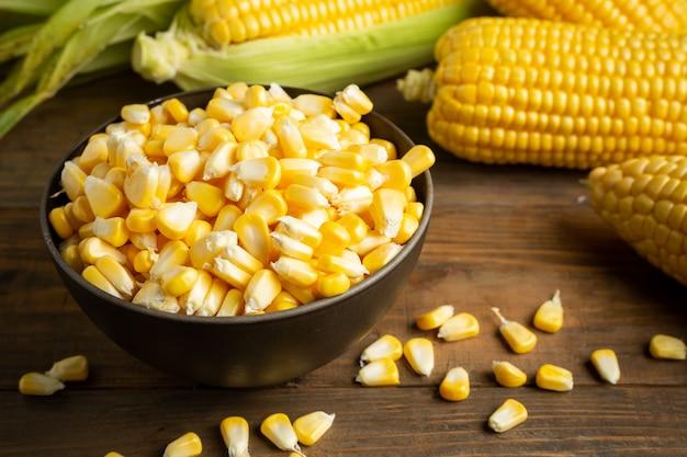 Semillas y maíz dulce en mesa de madera.