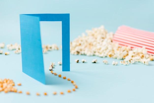 Semillas de maíz pasando por una puerta de papel azul que se convierte en palomitas de maíz sobre un fondo azul