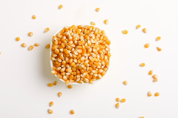 Semillas de maíz secas en un tazón en blanco