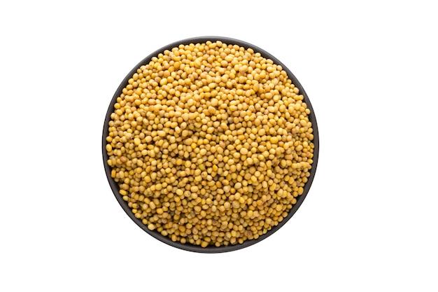 Semillas de mostaza en cuenco de arcilla aislado. vista superior de condimentos o especias