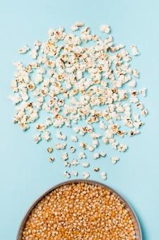 Semillas de palomitas de maíz en un recipiente con palomitas de maíz sobre fondo azul