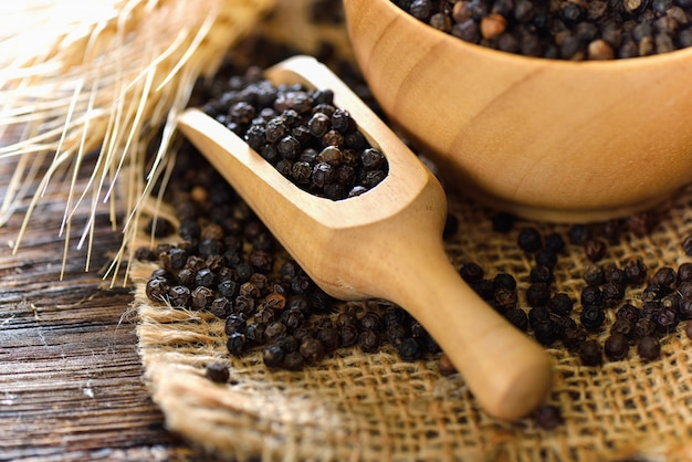 Semillas de pimienta negra en cuchara de madera sobre mesa
