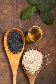 Semillas de sésamo blanco y negro y aceite en la mesa de madera