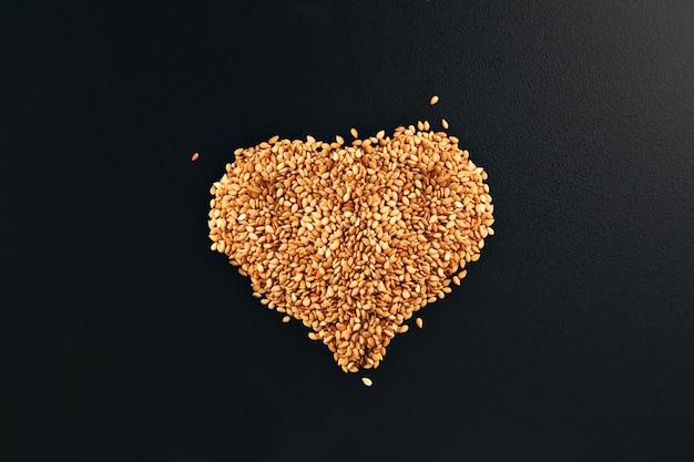 Semillas de sésamo blanco tostado dispuestas en forma de corazón sobre una superficie de mesa negra lisa