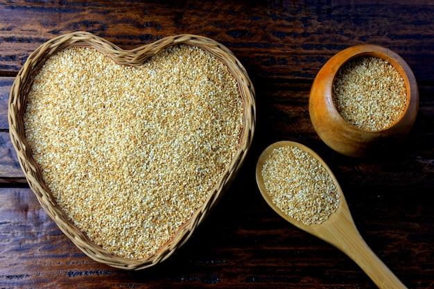 Semillas de sésamo en cesta con forma del corazón aislada en la tabla de madera rústica, visión superior.
