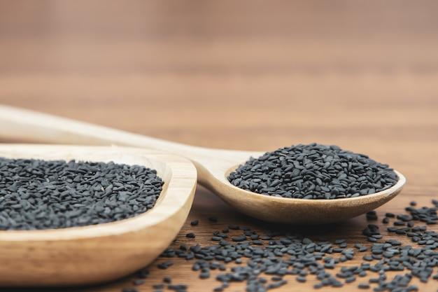 Semillas de sésamo negro en una cuchara de madera para una alimentación sana.