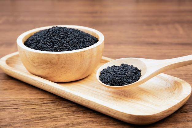 Semillas de sésamo negro en una cuchara de madera para conceptos de alimentación y dieta saludables.