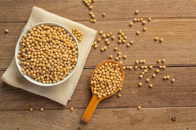 Semillas de soja sobre suelo de madera y sacos de cáñamo concepto de nutrición alimentaria.