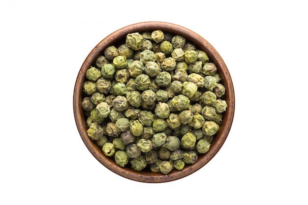 Las semillas verdes del grano de pimienta condimentan en el tazón de fuente de madera, aislado en blanco. vista superior de condimento