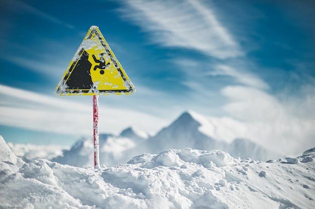 Señal de advertencia amarilla en el borde del precipicio, montañas de invierno y cielo azul de fondo