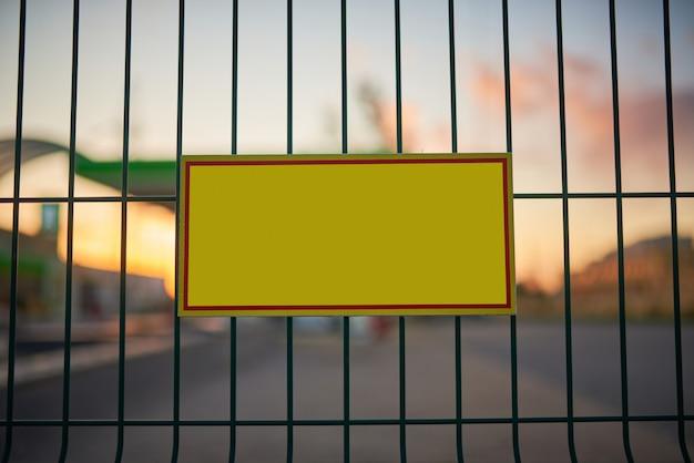 Señal de advertencia amarilla vacía en la cerca, ciudad borroneada al atardecer