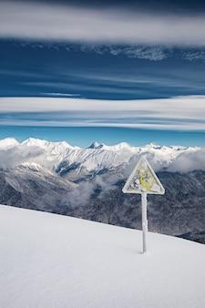 Señal de advertencia cubierto de nieve en el borde de la pista de esquí en las montañas