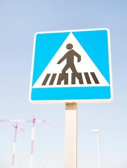 Señal de advertencia de peatones contra el cielo azul