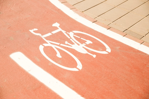 Señal de bicicleta blanca en carril bici
