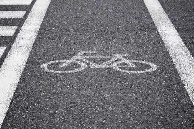 Señal de bicicleta pintada reflectante blanca, carril bici en la carretera para cruce peatonal