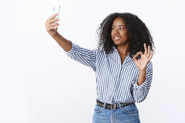 Señal bien imagen impresionante. atractivo, sociable, amistoso, moderno, milenario, chica de piel oscura, videollamada, novio, extender la mano que sostiene el teléfono inteligente mostrando el signo de ok sonriendo, selfie