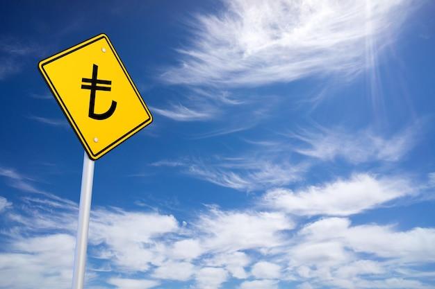Señal de carretera amarilla con signo de lira turca en el interior sobre fondo de cielo azul