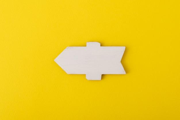 Señal de dirección de madera blanca sobre fondo amarillo.