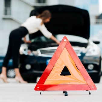 Señal de emergencia con coche en segundo plano.