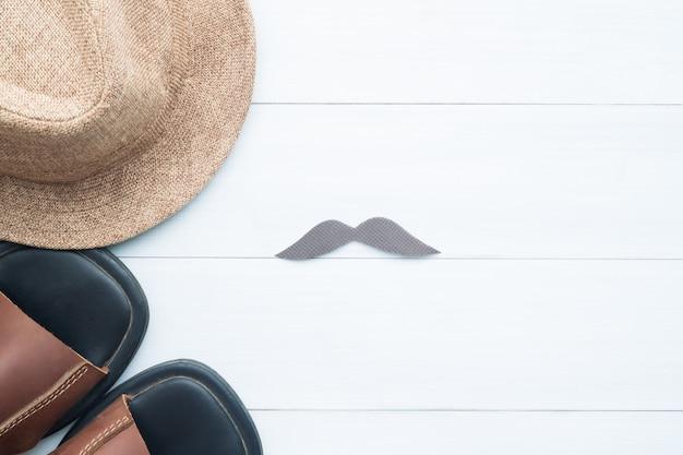 Señal de endecha plana creativa de bigote, sombrero de paja y zapatos en el fondo de madera blanca