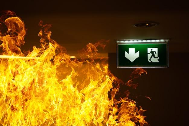Señal de escape en caso de incendio verde cuelga del techo con llamas alrededor