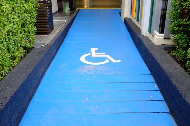 Señal de estacionamiento para discapacitados en camino de pendiente.